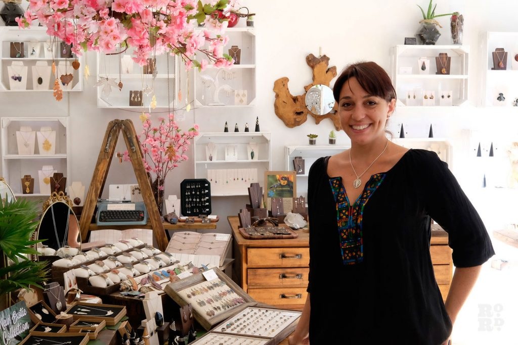 A designer stands in front of her jewellery display