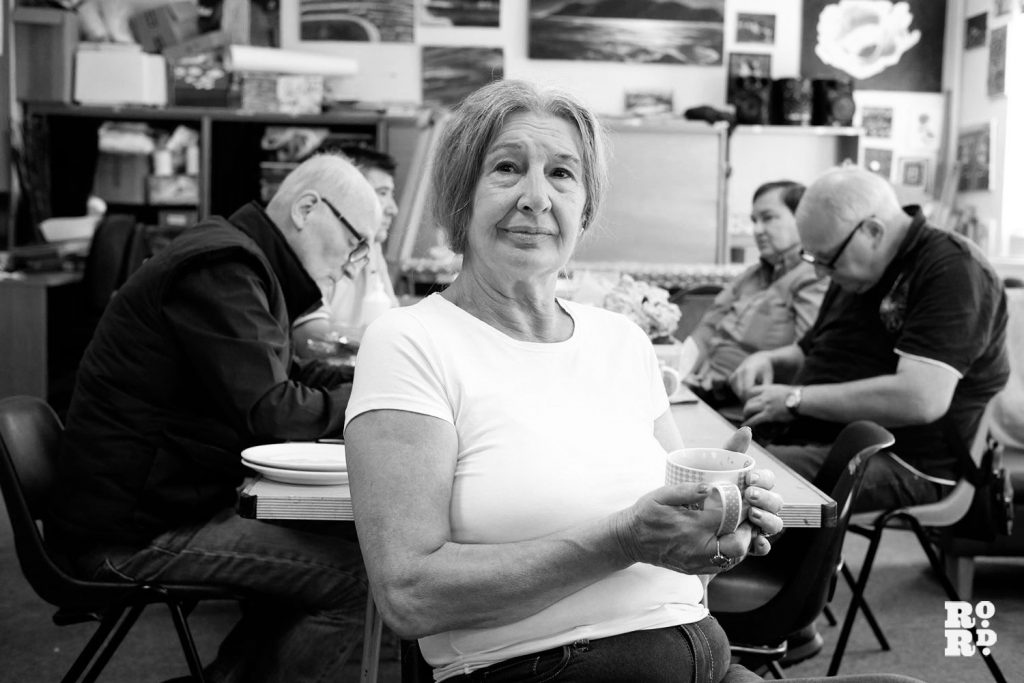 A smiling woman sits in a room with some other people, drinking a cup of tea