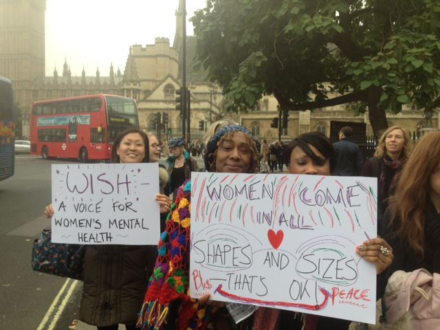 Women stand outside the Houses of Parliament demonstrating