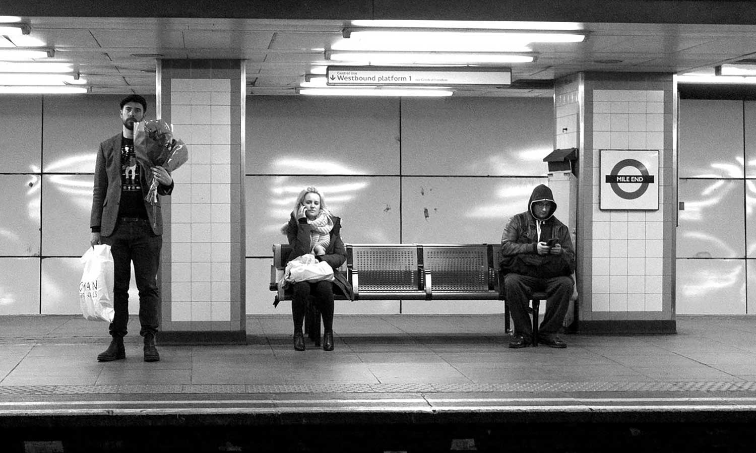 Three passengers on Mile End station, one man standing with a bunch of flowers, one woman sitting with bag on lap and another man in hooded top looking at his mobile phone.