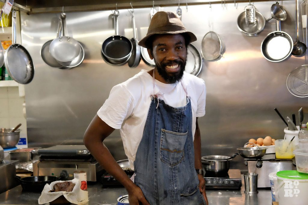 Man wearing hat and apron stands in stainless steel industrial style kitchen