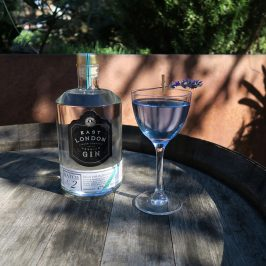 Bottle of gin on garden table next to cocktail in blue glass
