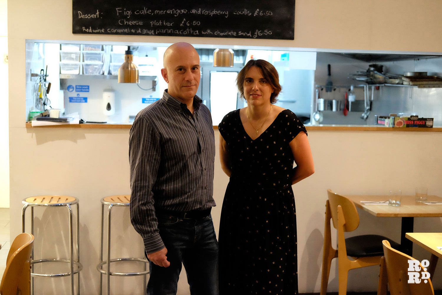 A man and a woman stand in front of the kitchen inside a restaurant