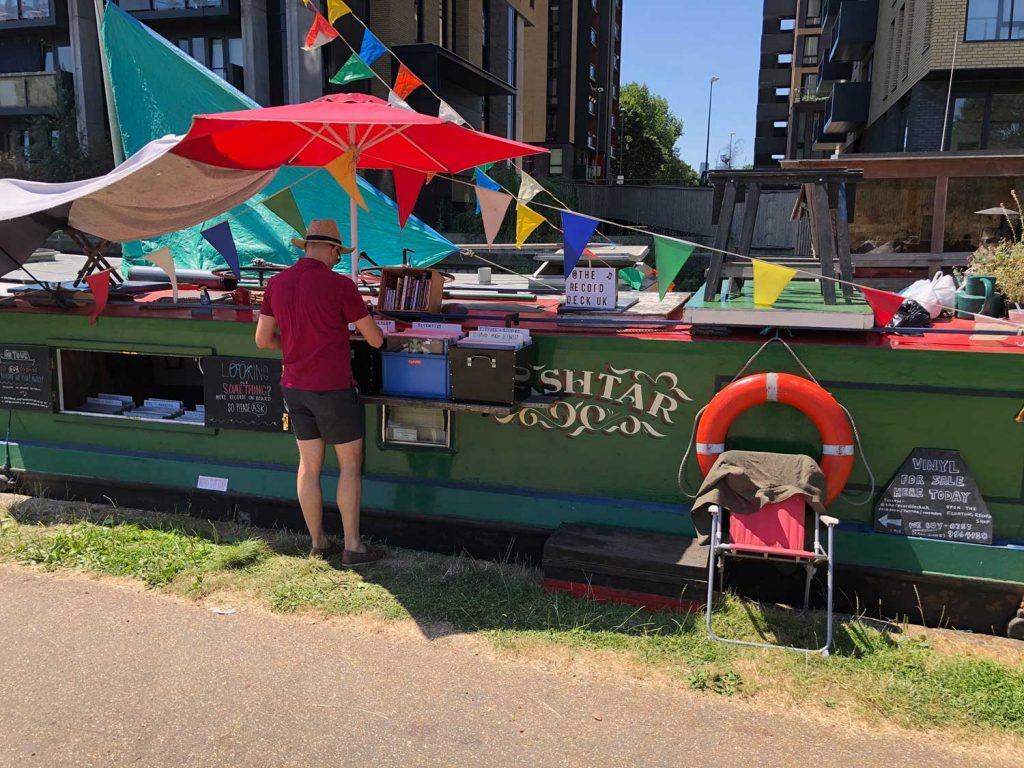 A customer browses records on record store barge on canal