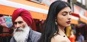 Street photo showing a young South Asian woman in traditional dress standing near a man in turban