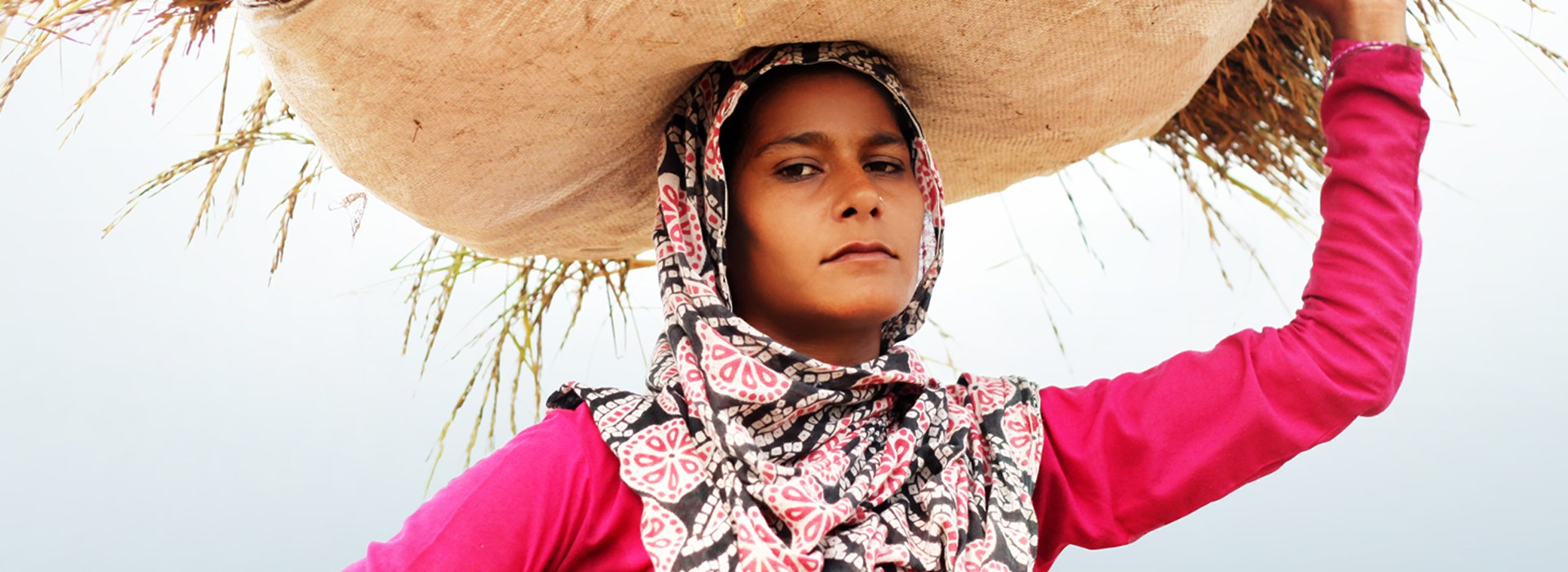 A young Indian woman carrying a basket on her head