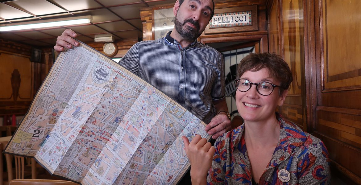 A man and a woman in a beautiful cafe display a map