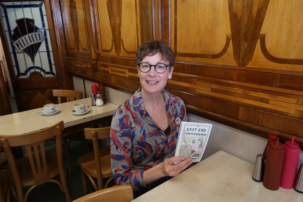 A smiling woman wearing glasses in a cafe holding a folded map