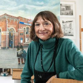 Doreen Fletcher artist posing in front of canvas painting
