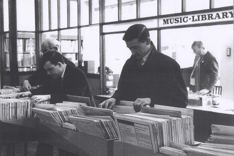 Men browsing vinyls in music library