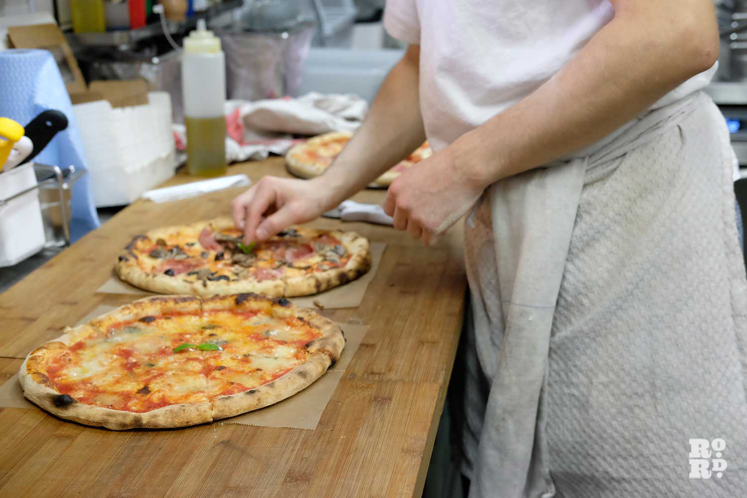 Pizza being prepared in a kitchen in Pizza Room in Mile End
