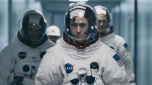 Ryan Gosling in astronaut suit walking through corridor