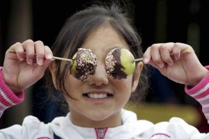 A girl holds toffee apples over her eyes