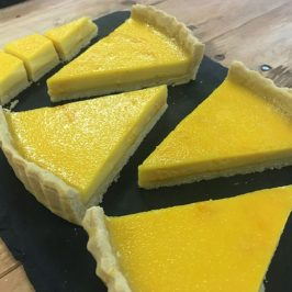 Five slices from a completed lemon custard tart