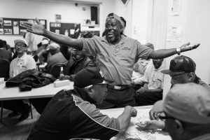 A man leaps to his feet in celebration while others around him continue playing dominoes