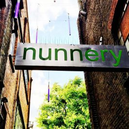 Sign for the Nunnery gallery hanging across Victorian alleyway in Bow East London