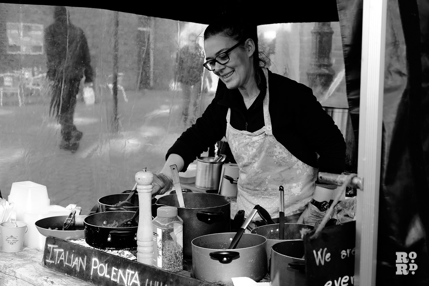 a woman serving food at a market stall
