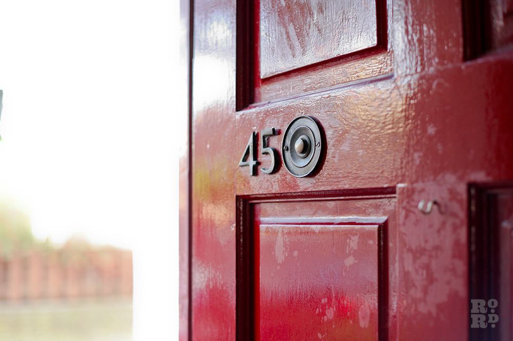 The red front door at 45 Norman Grove with traditional door furniture