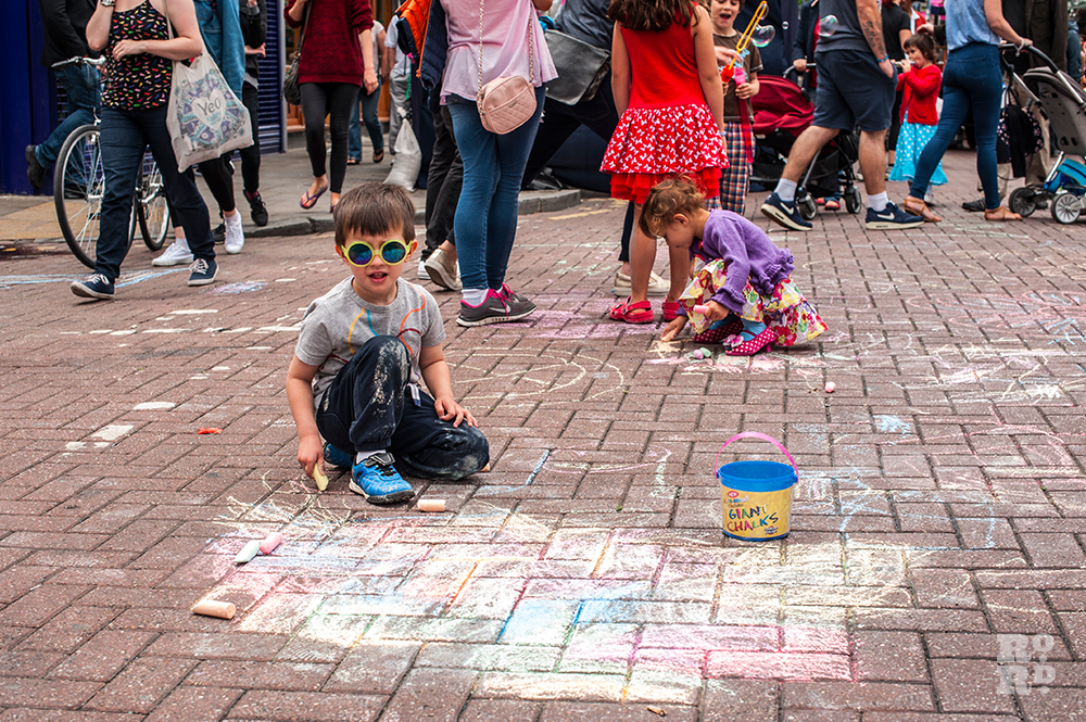 Children drawing on the pavement with chalk