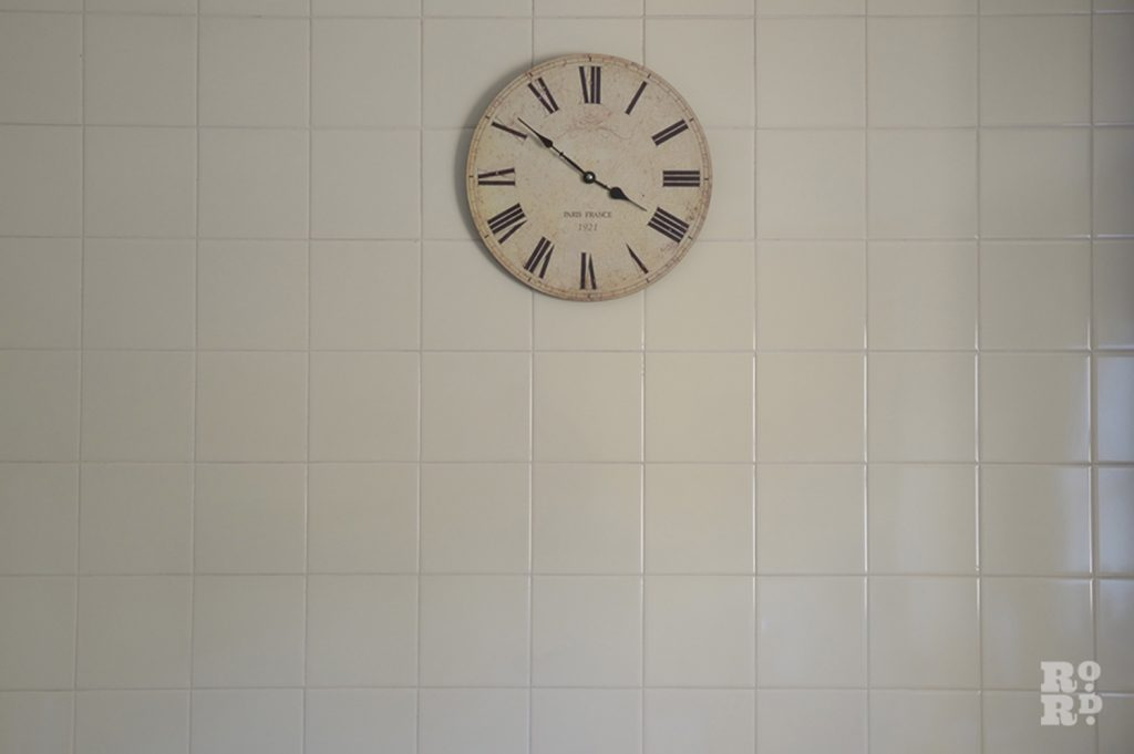Clock on a white tiled kitchen wall