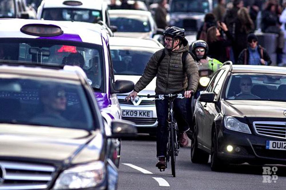 Cyclist surrounded by cars on highway