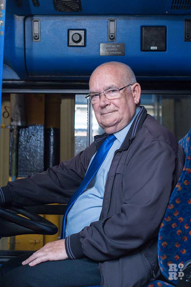 Driver, blue tie, sitting in driving seat of London bus