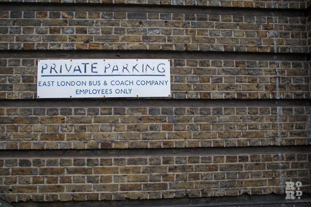 Private Parking notice on Victorian brick wall at Bow Bus Garage in East London