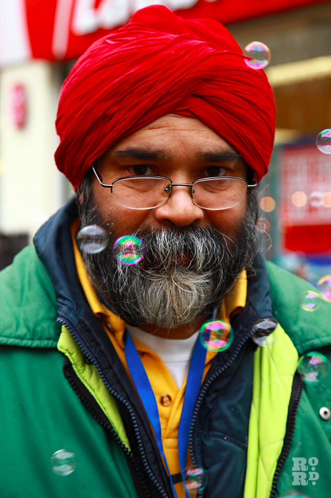Man wearing red Sikh turban with bubbles floating in the air.