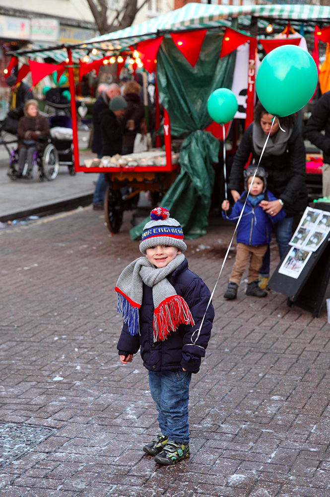Child with balloons at Roman Road Winter Festival