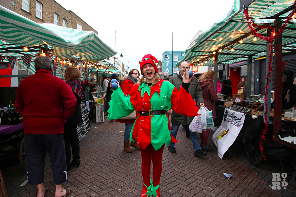 Juggler in festive red and green jester outfit.