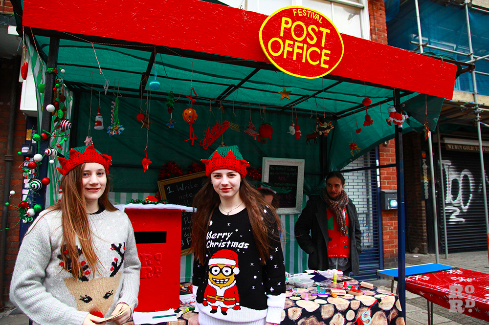 Girls in festive green and red knitted hats standing at post office market stall.