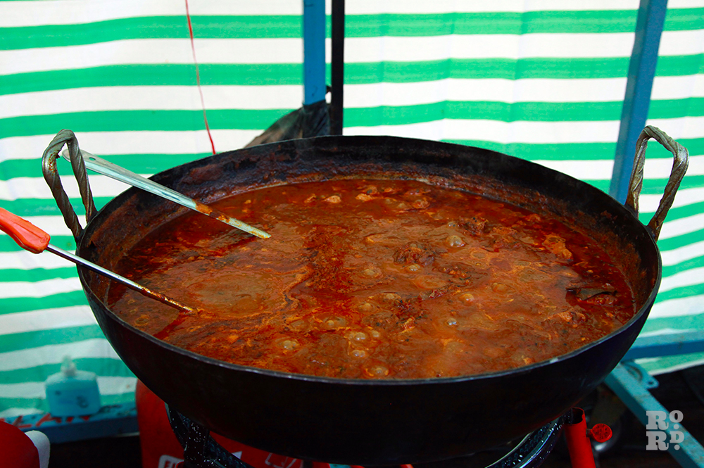Street food stall with green and white tarpaulin, and huge vat of curry stew.