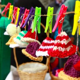 Knitted egg cosies hanging on line with colourful clothes pegs.