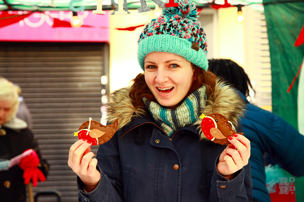Women in wooly hat and scarf holding two felt robin tree decorations.