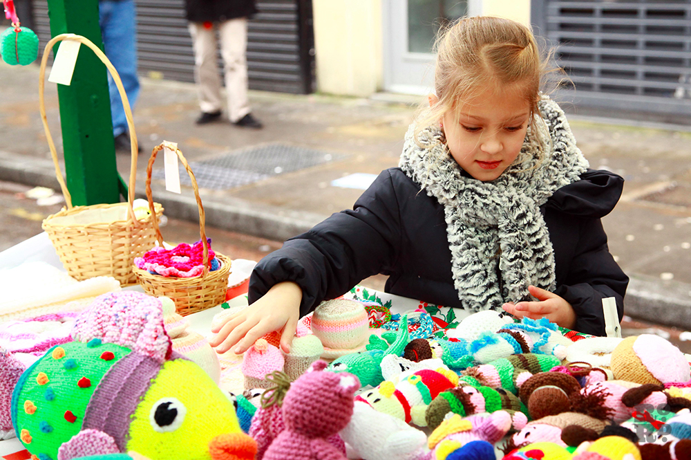 Girl looking longingly at knitted soft toys on a market stall.