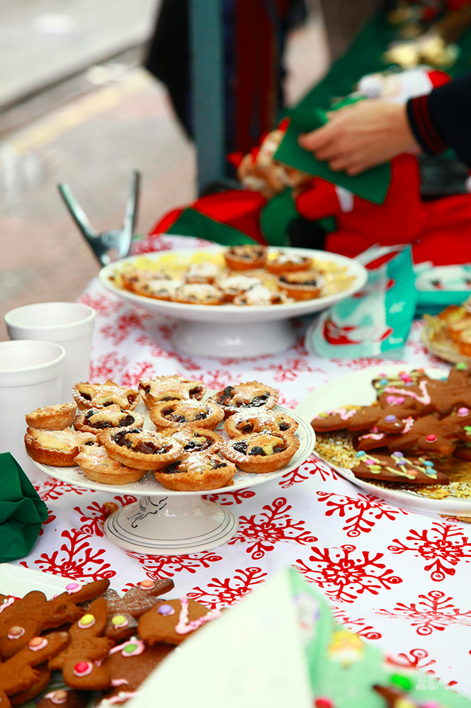 Cake stands with mince pies and gingerbread at a market stall.
