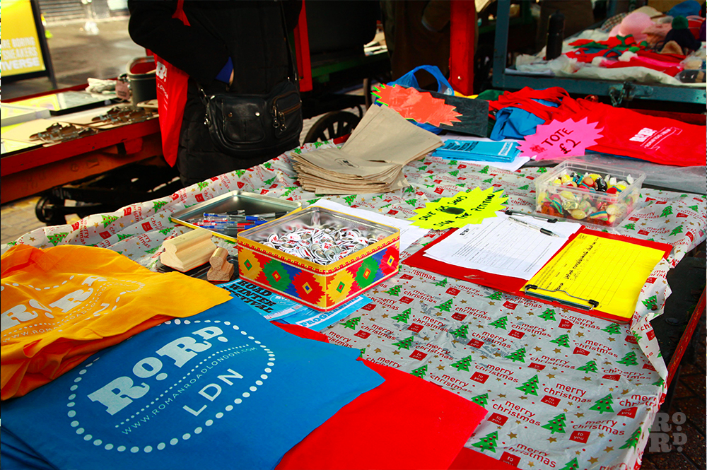 Market stall selling Roman Road LDN tote bags and pin badges.