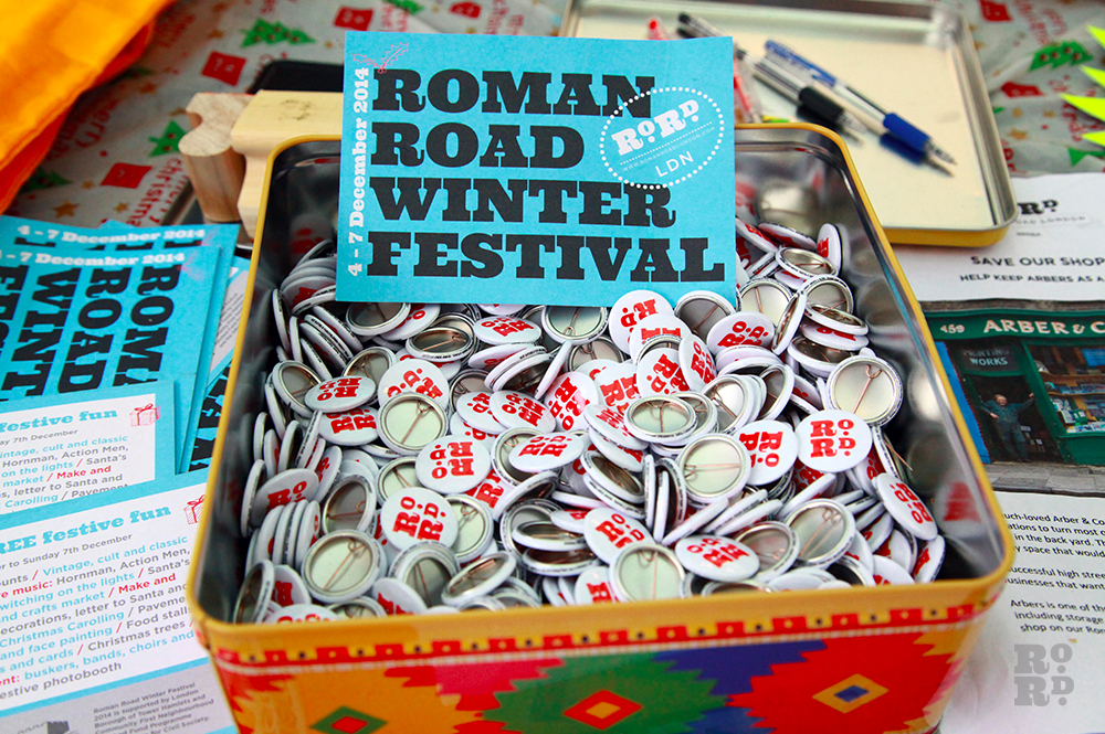 Vintage biscuit tin full of Roman Road LDN pins, with Roman Road Winter Festival postcard.