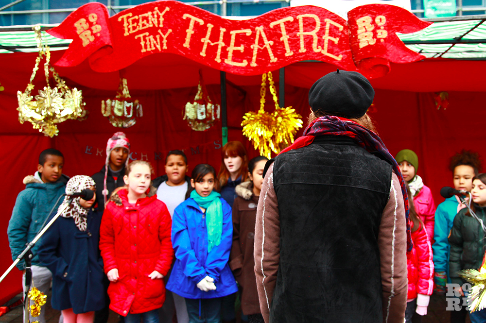 Children singing in makeshift outdoor theatre lined with red velvet and decorated with gold foil decorations.