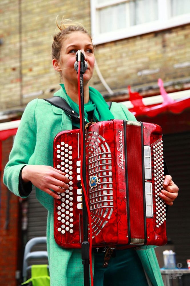 Wlomen in green coat busking with a red french accordion.