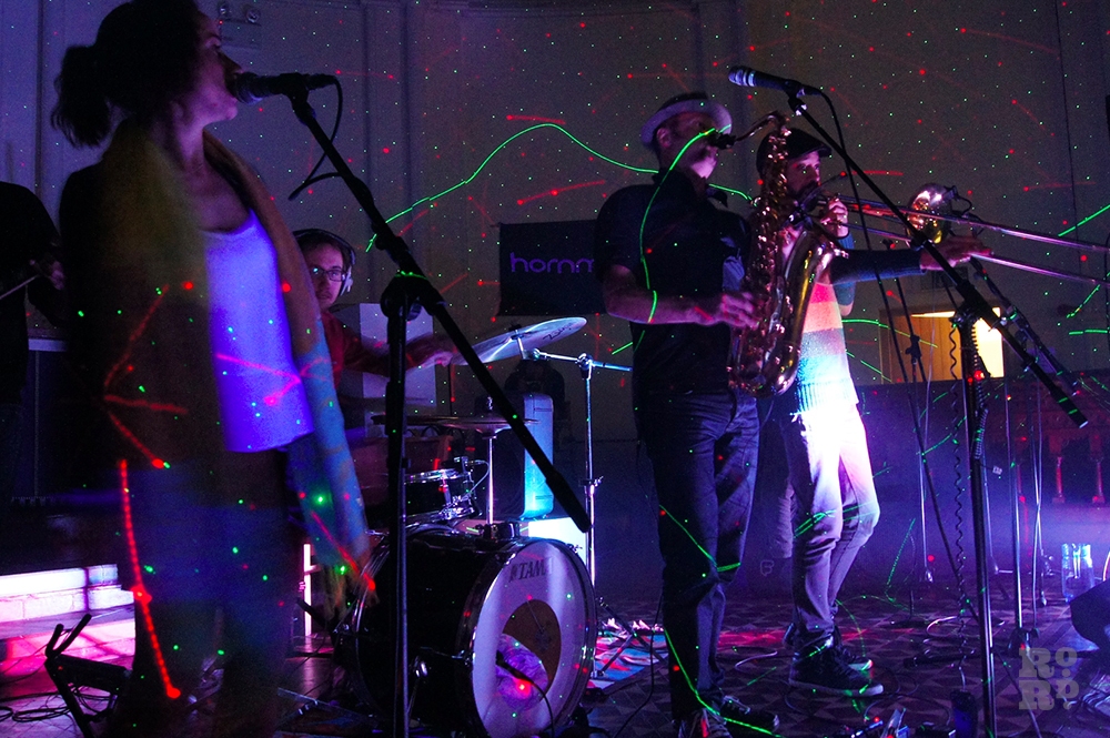 Musicians playing saxophone and trumpet, performing in Church with strobe lights.