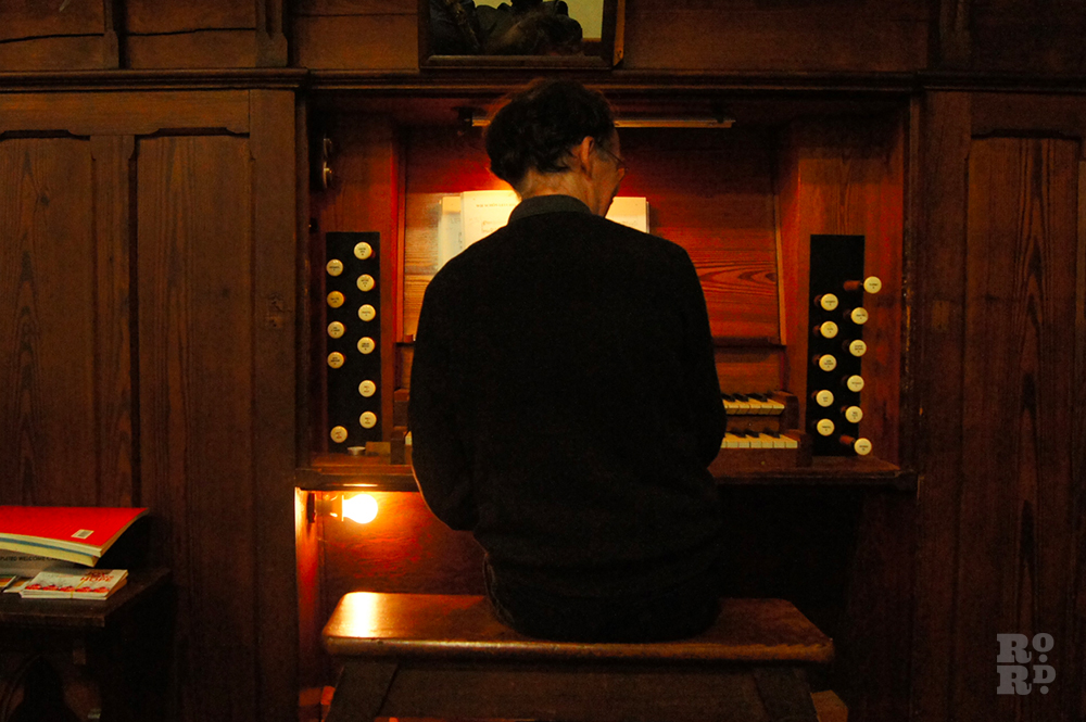Man dressed in black playing church organ.