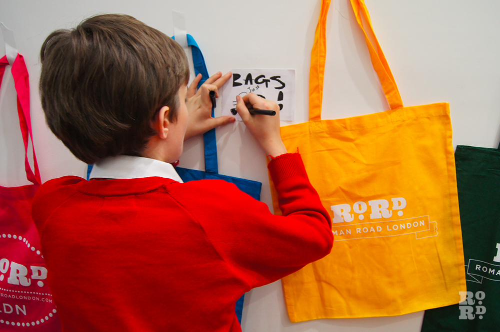 Boy in red jumper writing price tag for Roman Road LDN tote bags in bright colours.