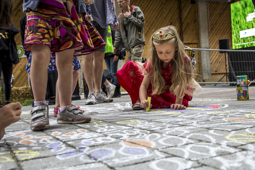 young girl drawing with chalk on pavement