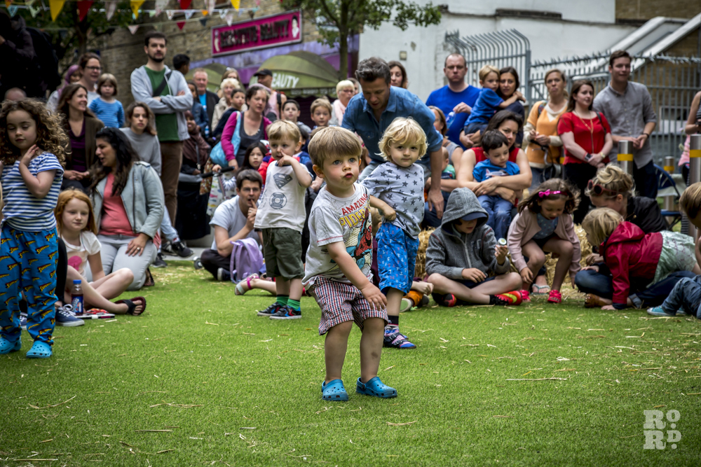 Children in the audience sitting on artiificial grass lawn