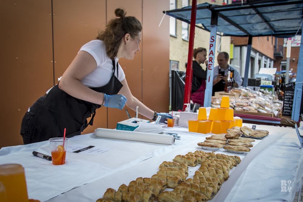 Sausage rolls and orange juice on market food stall