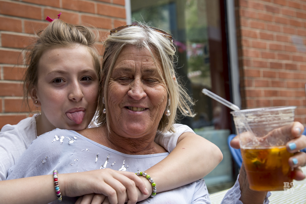 Young woman sticking out her tongue as she hugs her mother