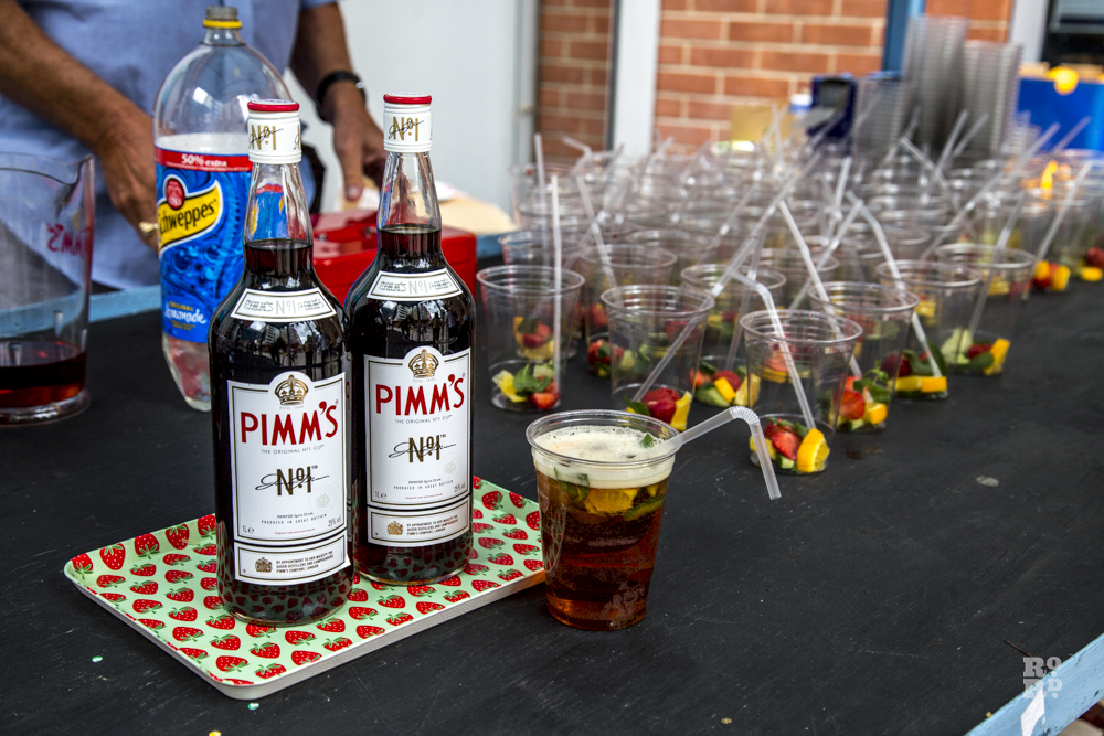 Pimms bar at Roman Road Festival with plastic cups in rows filled with fruit
