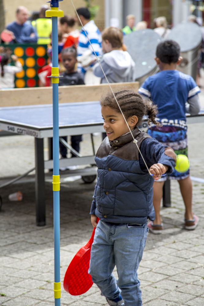 Girl playing swing ball with table tennis in background