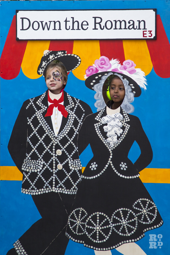 Two girls with heads poking through fairground Aunt Sally board of East End Pearly Queens